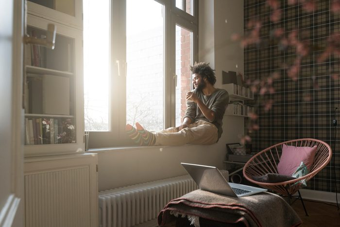 man sitting on window sill in living room looking outside