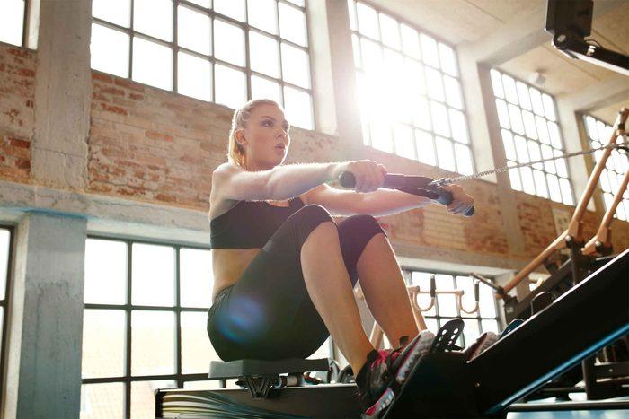 woman using rowing machine at gym