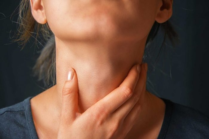 Woman holding her neck with her right hand.