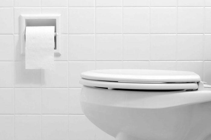 White bathroom with a white toilet and white tile wall.