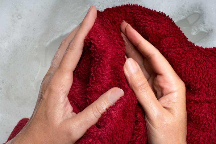 hands holding wet washcloth