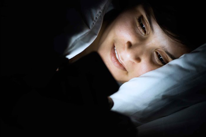 Woman looking at phone screen while lying in bed
