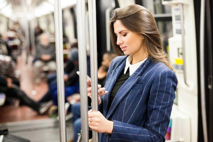 woman holding onto subway pole