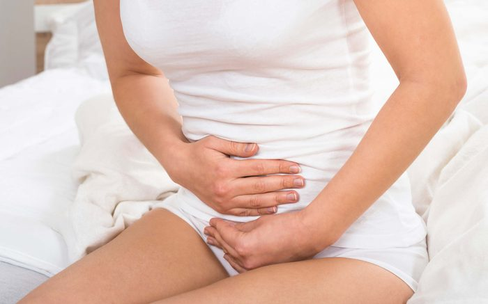 woman holding lower stomach and groin in pain
