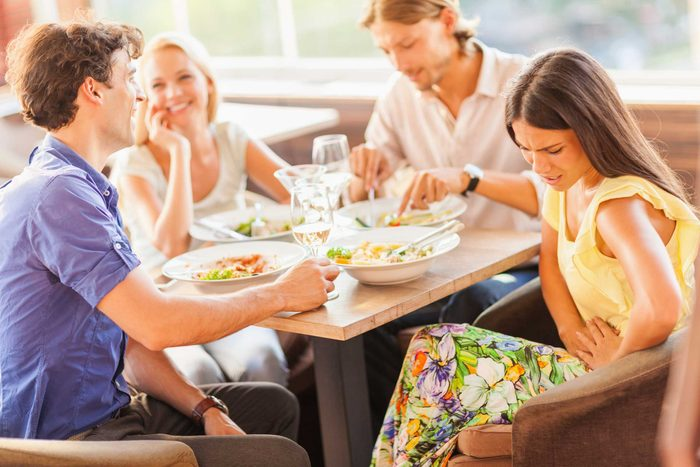 A family sitting around a table eating a meal together, while one woman is clutching her stomach as if in pain.