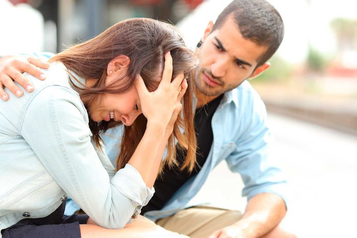 Man with hand on back of upset woman