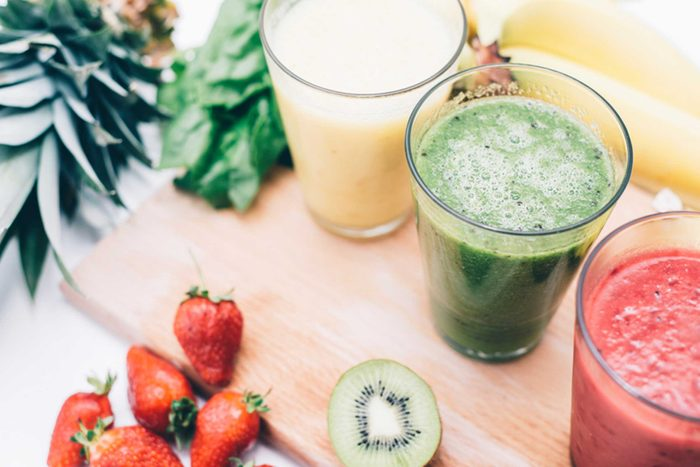 white, green, and red smoothies surrounded by fruit and veggies