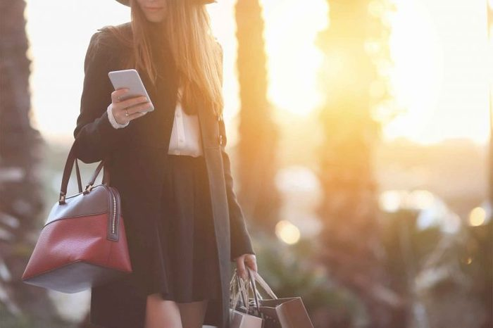 Woman wearing trendy clothing carrying shopping bags and looking at her phone as the sun sets behind her.