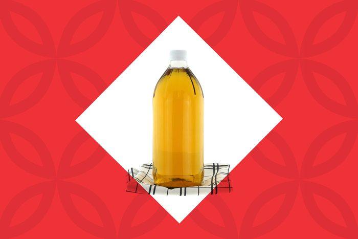 bottle of apple cider vinegar on a kitchen towel