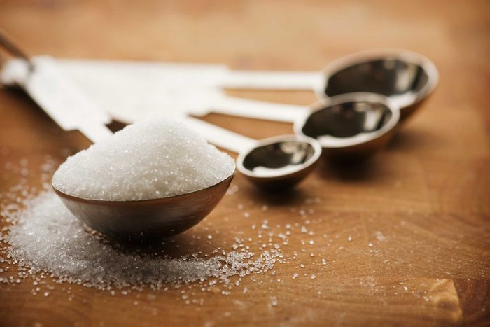 measuring spoons with tablespoon full of sugar