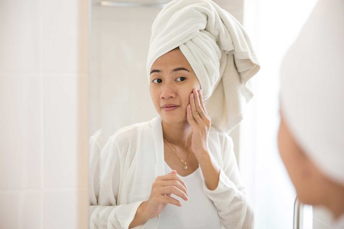 woman rubbing her face in mirror