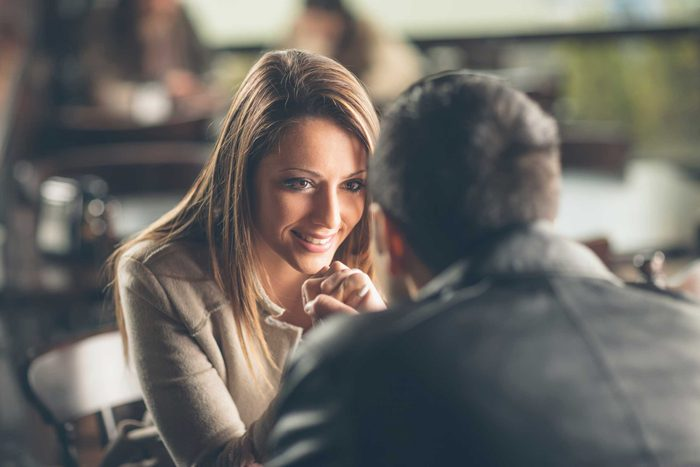 Woman smiling at man, sitting at a table