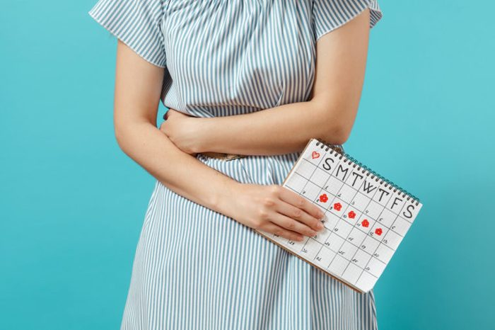 woman holding stomach with menstrual calendar period