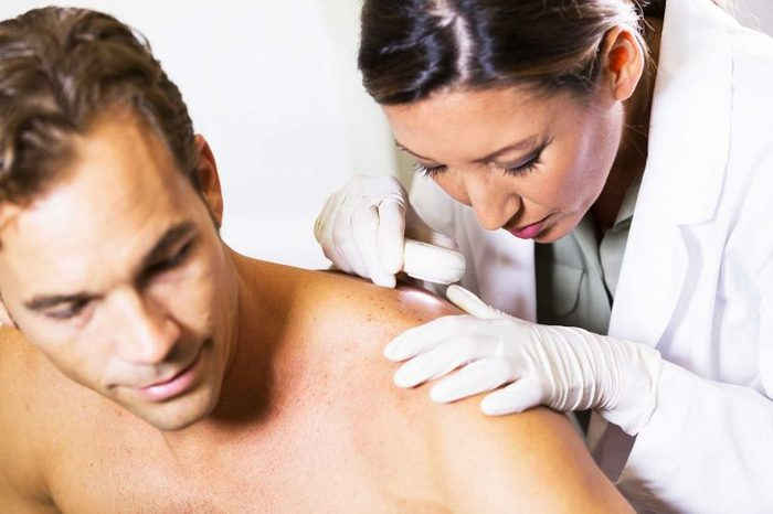 Doctor examining a man's back in the doctor's office.