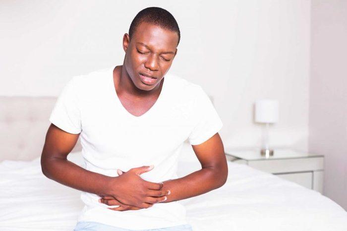 Man clutching aching belly
