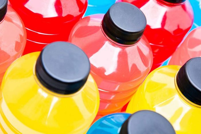 Bottles of red, yellow, and blue sports drinks.