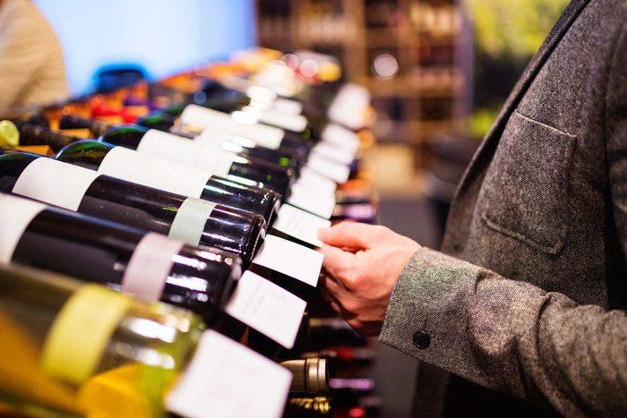 man checking prices on bottles of wine