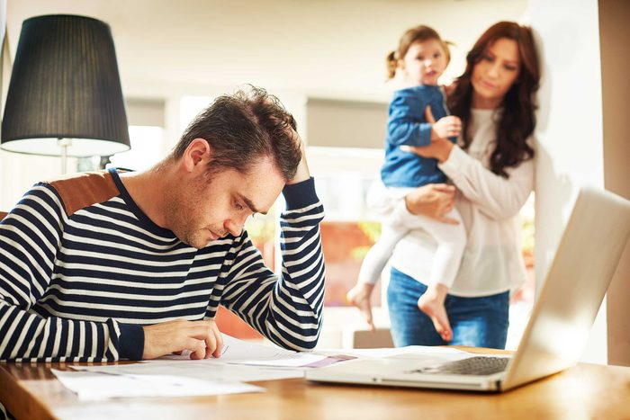 Man at his desk at home looking stressed as he reviews paperwork.
