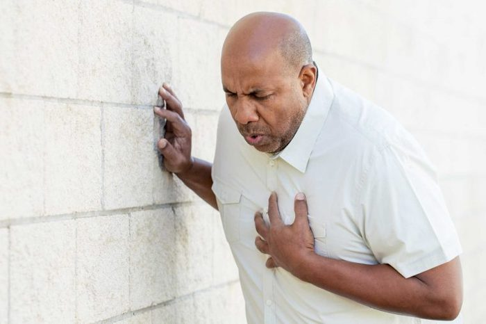 Man in a white shirt clutching his chest and leaning on a wall.