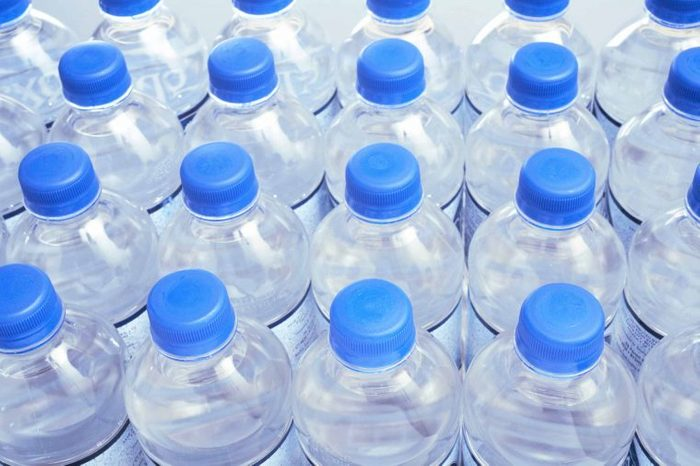 Picture of rows of clear water bottles with blue plastic lids