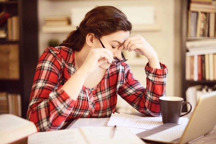 tired woman holding the bridge of her nose in front of a laptop