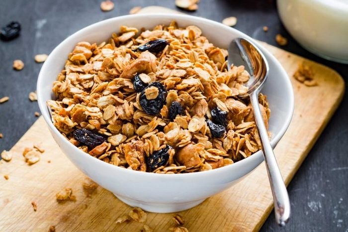 Bowl of granola and dried blueberries with a spoon in it, resting on top of a wooden cutting board.