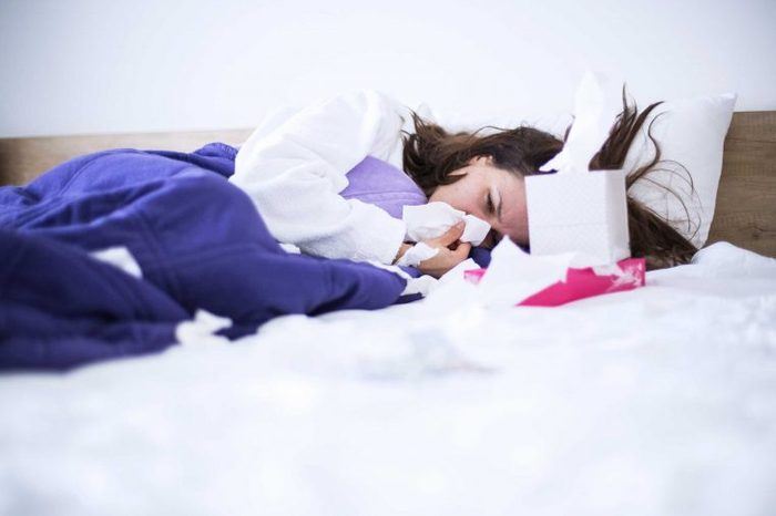 Woman in bed with a box of tissues, blowing her nose.