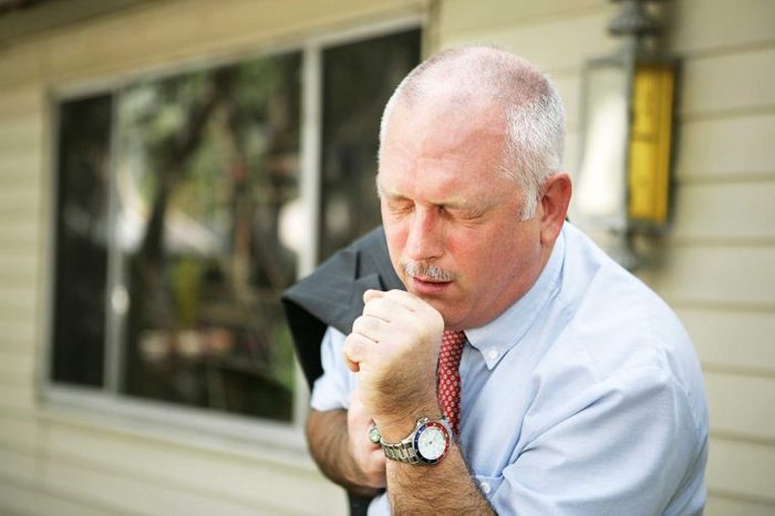 Man in work dress coughing into his hand.