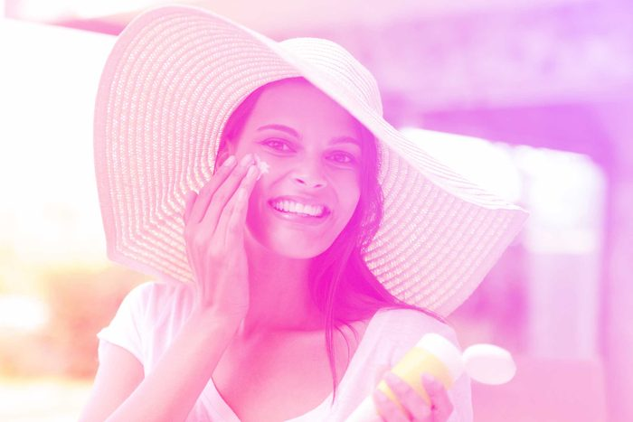 woman in a sun hat, smiling and applying sunscreen