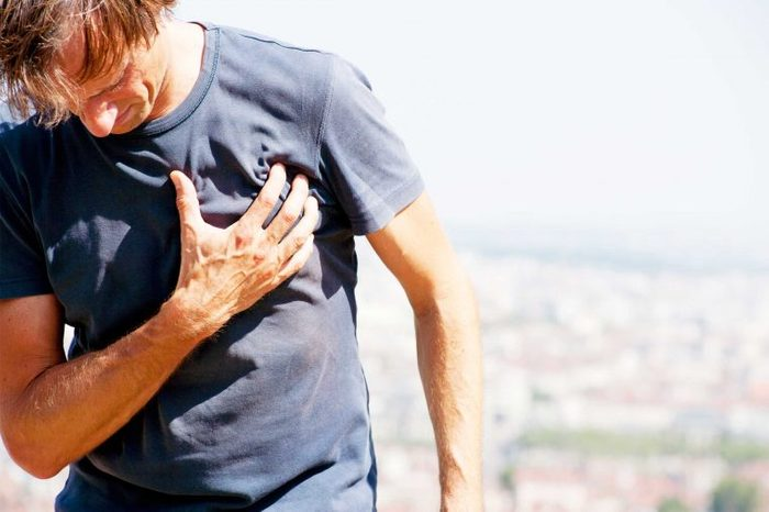 Man outside clutching his chest.