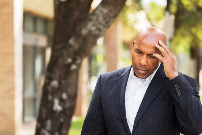 Man in a suit outside holding his head as if having a headache.