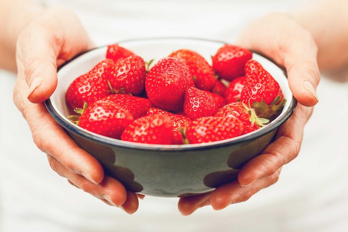 hands holding a bowl of strawberries