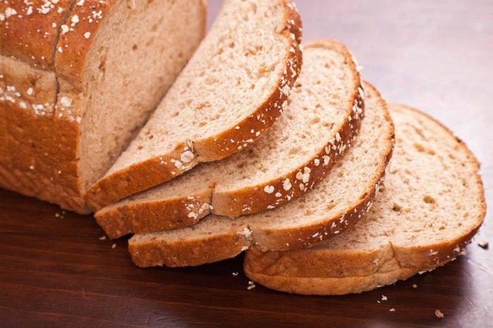 Sliced multigrain bread on a wooden tabletop.