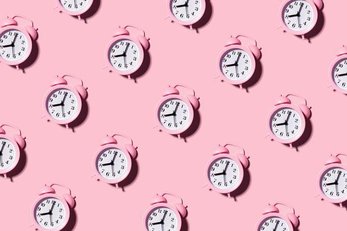 pink alarm clocks on pink background