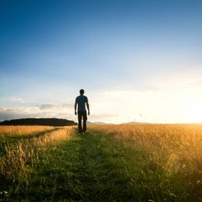 man walking alone through field enjoying nature and the outdoors