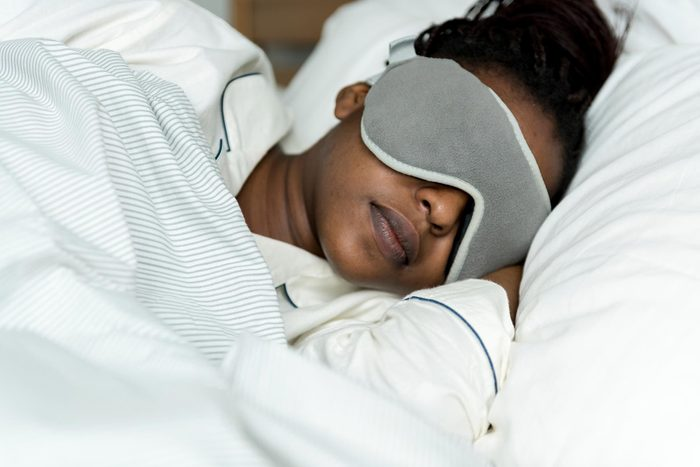 African-American woman with sleep mask in bed