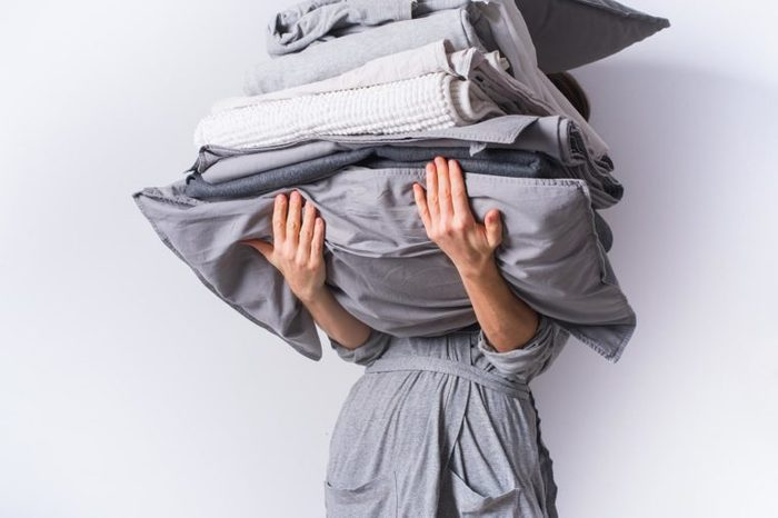 woman holding a stack of bedding