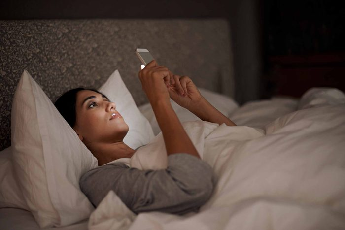 woman reading a smart phone in bed at night