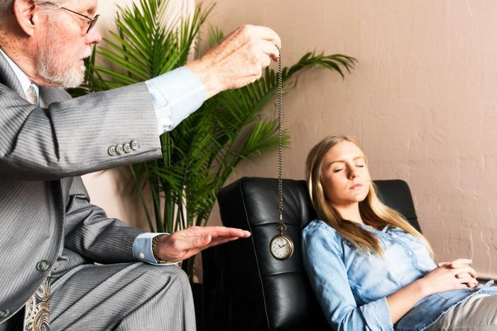 Hypnotist dangling a watch in front of his patient.