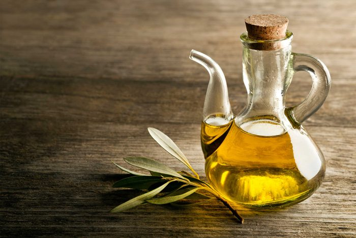 glass olive oil pourer filled with olive oil