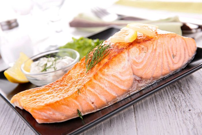 cooked salmon filet on a plate with dill sauce and lemon wedge