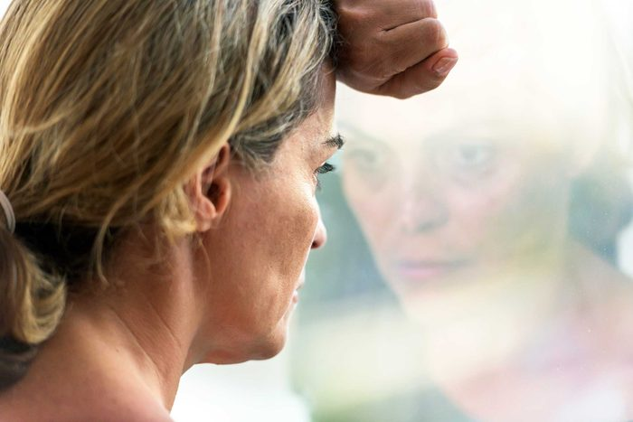 dejected woman staring out a window