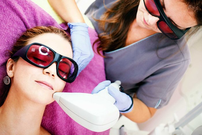 woman and doctor wearing protective glasses; the patient is getting laser skin treatment