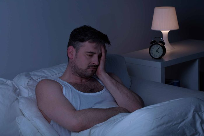 man sitting up in bed at night, holding his head