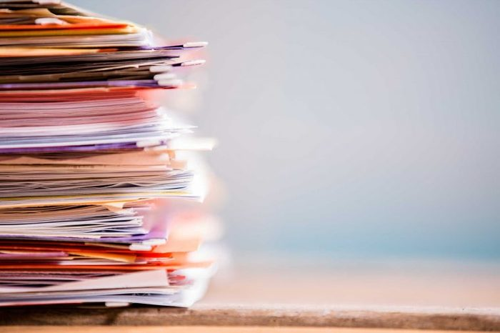 A stack of papers and folders on a desk.