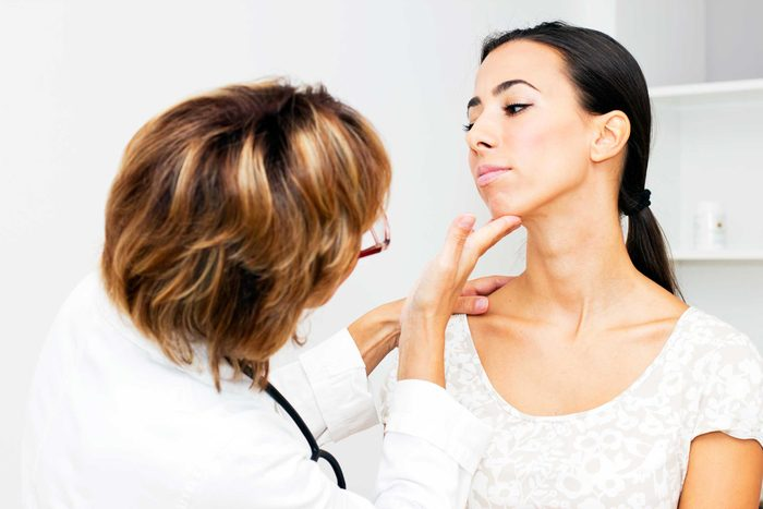 doctor checking a woman's chin and throat