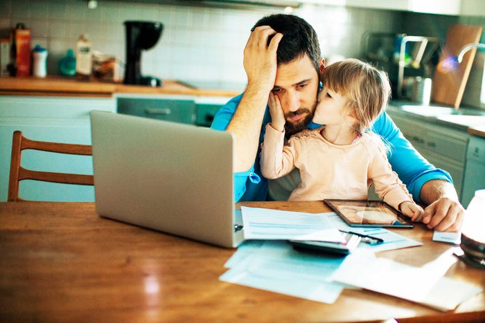 stressed father in front of computer, daughter in lap kissing him