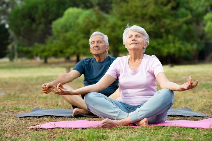 senior couple doing yoga deep breathing outside together