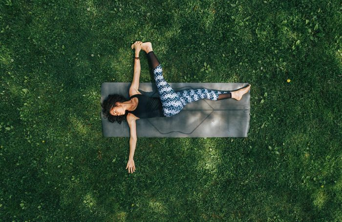 overhead shot of woman doing yoga in the park