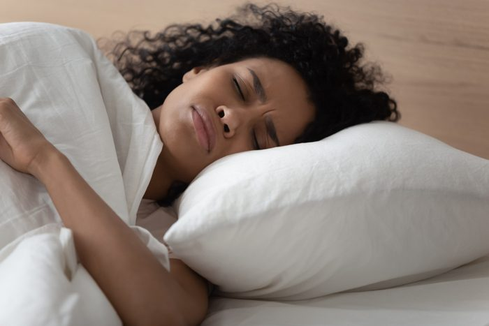 woman lying in bed uncomfortable